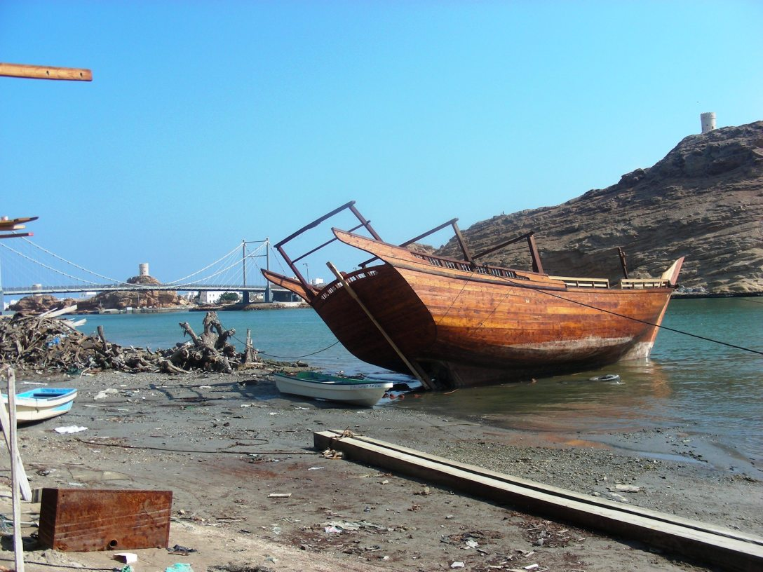 A dhow waiting to mark its entry into the waters at Sur, Oman. Note the restored lighthouse tower